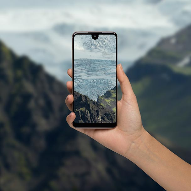 Hand manipulating a View 2 smartphone with mountains in background